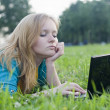 Pretty woman with laptop on the green grass — Stock Photo #6128344