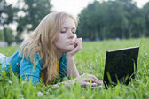 Pretty woman with laptop on the green grass — Stok fotoğraf