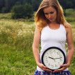 Young woman with a wall clock — ストック写真