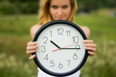 Young woman with a wall clock — Stock Photo