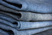 A pile of different types of blue denim jeans closeup — Stock Photo