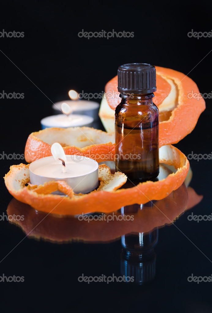 Bottle of aromatic essence, orange,andles.  Stock Photo #5448558