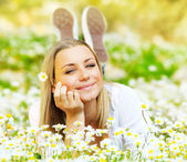 Beautiful female laying on the flower filed — Stock Photo