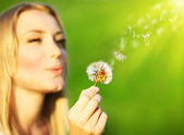 Happy beautiful girl blowing dandelion — Stock Photo