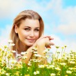 Beautiful female laying on the flower field - Stock Photo