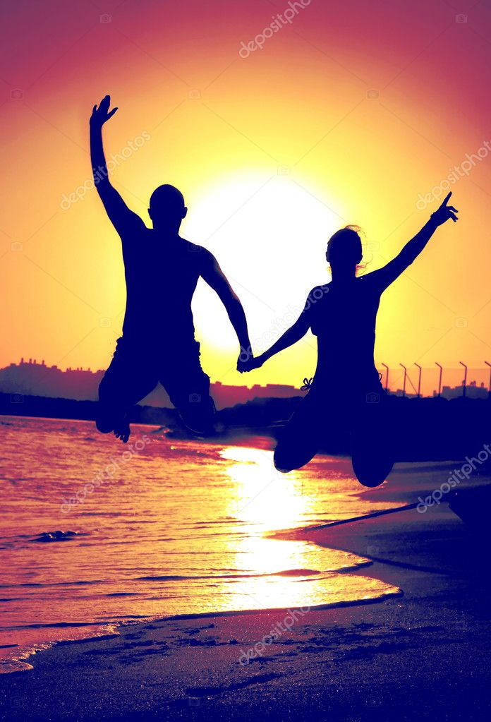 Two happy jumpers on the beach at sunset — Stock Photo #6114355