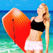 Happy sporty girl playing body board on the beach - Stock Photo