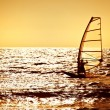 Windsurfer silhouette over sea sunset - Stock Photo