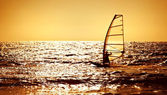Windsurfer silhouette over sea sunset — Stock Photo