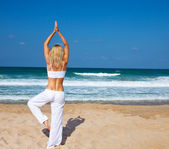 Healthy yoga exercise on the beach — Stockfoto