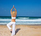 Hälsosam yoga övning på stranden — Stockfoto