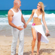 Happy couple walking on the beach — Stock Photo