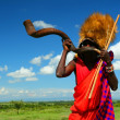 Masai warrior playing traditional horn - Stock Photo