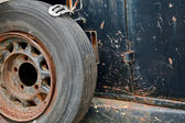 Rusty wheel on the side of an old car — Stock Photo