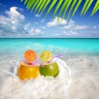 Coconut cocktails juice in tropical beach water splash — Stock Photo