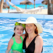Mother and daughter hug in pool tropical beach — Stock Photo