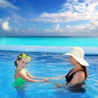 Daughter and mother in swimming pool tropical — Stock Photo #5394775