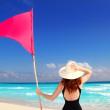 Beach rear woman holding red beach flag pole — Stock Photo