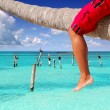 Caribbean inclined palm tree beach tourist legs - Stock Photo