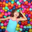 Little girl playing lying in colorful balls park playground - Stock Photo