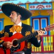 Charro Mariachi playing guitar Mexico houses - Stock Photo
