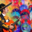Charro Mariachi playing guitar over colorful blur — Stock Photo #5397461