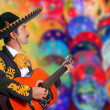 Charro Mariachi playing guitar over colorful blur - 