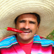 Stock Photo: Mexican man poncho sombrero eating red hot chili