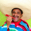 Mexican man poncho sombrero eating red hot chili — Stock Photo