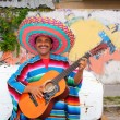 Stock Photo: Mexican humor man smiling playing guitar sombrero