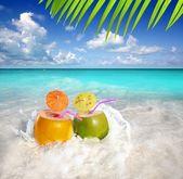 Coconut cocktails juice in tropical beach water splash — Stock Photo