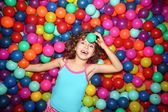 Little girl playing lying in colorful balls park playground — Stock Photo