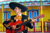 Charro Mariachi playing guitar Mexico houses — Stock Photo