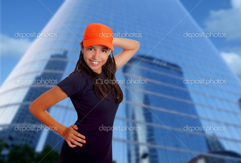 Beautiful Latin teen hispanic girl orange cap posing mirror city skyscraper