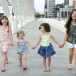 Four little girl group walking in the city — Foto de stock #5494827