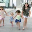 Four little girl group walking in the city — Stockfoto