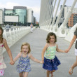 图库照片: Four little girl group walking in the city