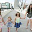 Foto Stock: Four little girl group walking in the city
