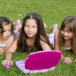 Three little girl playing with toy computer in grass — Stock Photo #5494840
