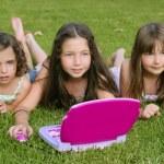 Три маленькая девочка играет с игрушкой компьютер в траве — Стоковое фото
