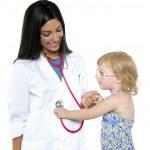 Brunette pediatric doctor with blond little girl — Stock Photo