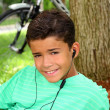 Teen smiling boy hearing music headphones grass - Stock Photo