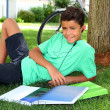 Teen smiling boy studying book garden headphones — Stock Photo