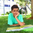 Royalty-Free Stock Photo: Boy teen studying laying green grass garden