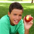 Boy teenager eating red apple on garden grass — Stock Photo