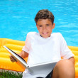 Boy student teen vacation homework pool float — Stock Photo