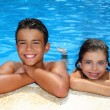 Teen boy and little girl summer vacation in blue pool — Stock Photo