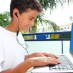 Teenager student happy boy laptop earphones — Stock Photo
