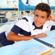 Boy teen sailor laying on marina boat chart map — Stock Photo