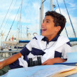 Boy teen sailor laying on marina boat chart map - Stock Photo